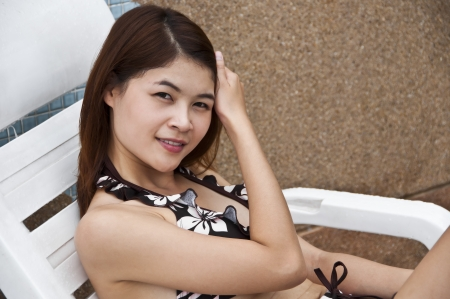Beautiful Asian woman on poolside chair  Stock Photo