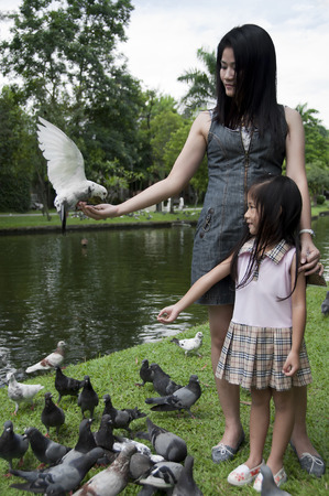 Little Asian girl and mom enjoy feeding pigeon