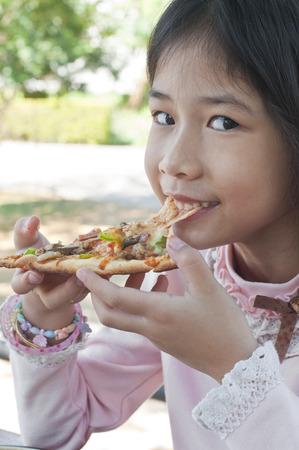 Little Asian girl enjoy eating pizza  photo