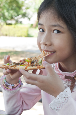 Little Asian girl enjoy eating pizza  Stock Photo