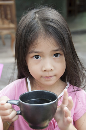 Little Asian girl with a cup of cocoa  Stock Photo