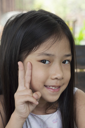 hand sign: Little Asian girl with victory hand sign