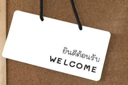 thai language: English - Thai welcome sign label on wooden board