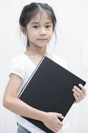 Asian little girl hold big black textbook  photo