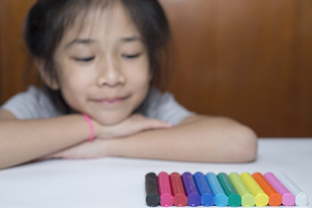 Little Asian girl looking at colorful plasticine.
