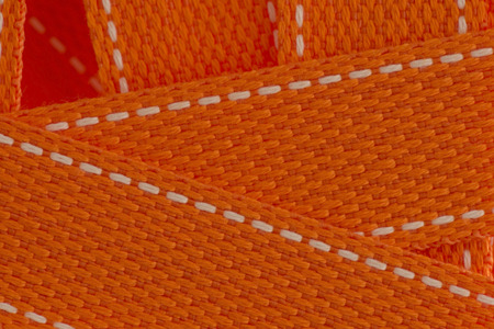 lashing: Orange strap belt macro closeup as background.