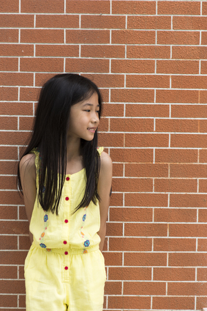 Little Asian girl portrait against brick wall. photo