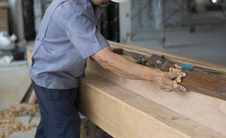 Carpenter using plane tool in workshop. Stock Photo
