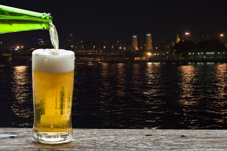 Enjoy beer with night landscape on Chao Phraya River, Bangkok Thailand.