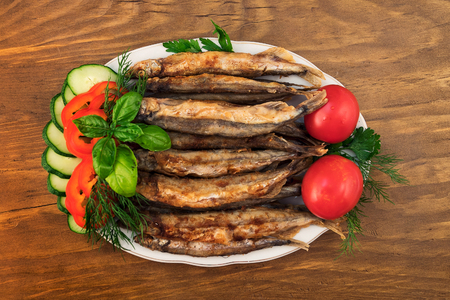 Fried capelin, laid on a plate with tomatoes, slices of cucumbers, sliced pepper, dill, parsley and basil  leaves. Stock fotó