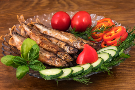 Capelin, completely fried in oil until golden  brown, laid on a plate, decorated with sliced cucumbers, sweet pepper, a sprig of green basil  and dill. Stock fotó
