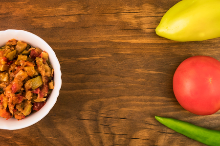 A mixture of stewed vegetables from courgettes, tomatoes, carrots, pepper in a plate on a wooden background with whole fruits, top view.