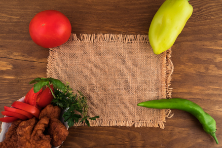 A piece of fabric on a wooden background, next in a plate of battered fish and whole vegetables, top view, for the recipe.