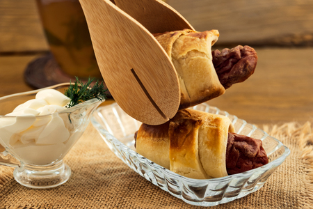 Baked puff pastry rolls stuffed with meat sausages in a glass plate, wooden kitchen tongs, sour cream sauce with dill, linen cloth napkin, all on a wooden background. 스톡 콘텐츠