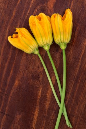 Three flowers with yellow petals on wooden background, top view, vertical frame.