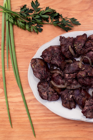 Pieces of liver stew on a white porcelain plate, next to a wooden background green onions and a sprig of parsley. Stock fotó