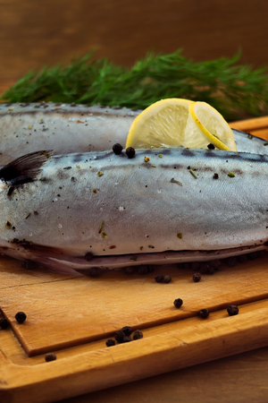 Mackerel with lemon and black pepper on a chopping board. Stock Photo