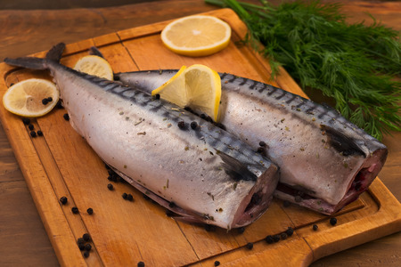 Mackerel with lemon, dill and black pepper on a chopping board.