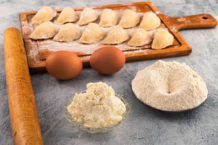Cottage cheese in a round plate, flour, chicken eggs-ingredients for cooking dumplings with filling.