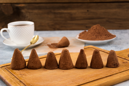 Chocolate truffles stacked in a row on a wooden background, white mug with tea, cocoa powder in a plate. Stock Photo