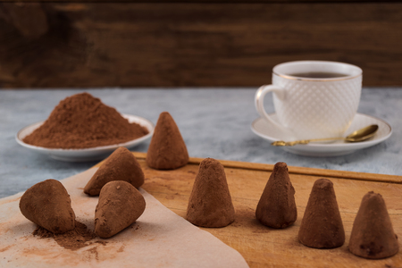 Chocolate truffles sprinkled with cocoa powder, white mug with tea.