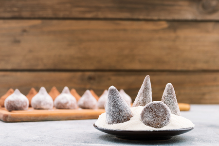 Chocolate truffles sprinkled with white powdered sugar, wooden background, copy space. Archivio Fotografico
