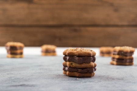 Breakfast cookies with chocolate filling, wooden background, copy space.