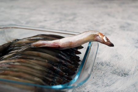 One small fish is selected from glassware, where the fish will be baked.