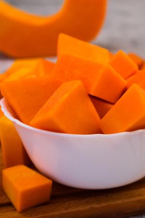 Cubes sliced pumpkin in a white plate. Vertical. Vegetarian food. Raw vegetables.