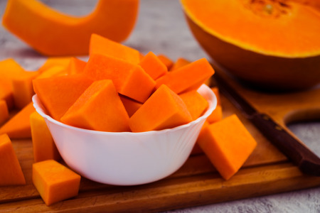 Sliced pumpkin cubes in a white bowl. Orange flesh of ripe fruit. Vegetarian food. Raw vegetables. Stock Photo