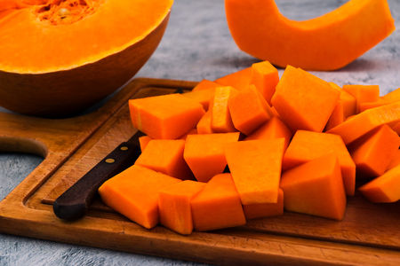 Pieces of ripe pumpkin on the kitchen Board. Orange pulp. Raw vegetables. Vegetarian food. Imagens