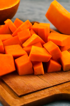 Preparation of raw pumpkin. Pieces of orange pulp on a wooden Board. Vegetarian food. Raw vegetables. Light background. Imagens - 113086532