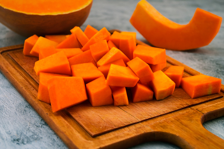 Pieces of orange pumpkin on the cutting Board. Raw vegetables. Vegetarian food. Light background. Stock fotó