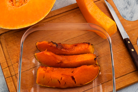 Cooked in the oven ripe pumpkin. Slices of orange flesh with skin. Vegetarian food.