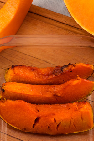 Slices of baked pumpkin in a glass bowl. Wooden background. Vegetarian food. Vertical.