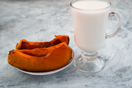 Delicious dessert. A glass of milk and a baked pumpkin. Light background.