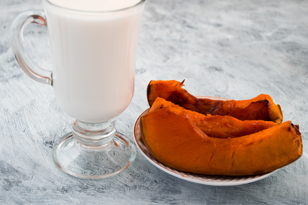 Baked pumpkin on a plate. Glass of milk. Light background. Diet food. Imagens