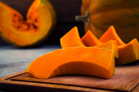 Sliced pumpkin. Ripe orange in the middle. Wooden board. Light background. Vegetarian food. Imagens - 113086902