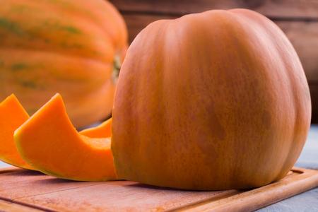 Orange big pumpkin. Cut slices. Kitchen cutting Board. Light background. The orange pulp of the fruit. Ripe vegetables.