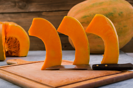Slices of pumpkin are in line for roasting. Kitchen cutting Board. Orange flesh of ripe fruit. Raw vegetables. Light background.