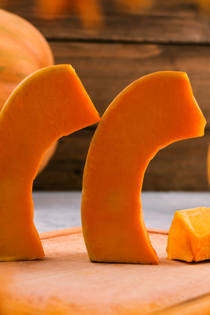 Pieces of raw pumpkin on a wooden Board. Line to eat. the orange pulp of the fruit. Vertical. Imagens