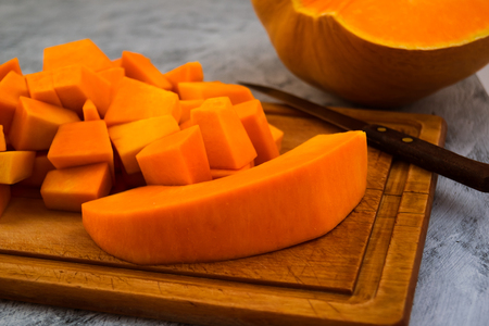 Cooking pumpkin. Cutting into pieces of ripe flesh. Kitchen cutting Board. Vegetarian food. Raw vegetables. Imagens - 113087110