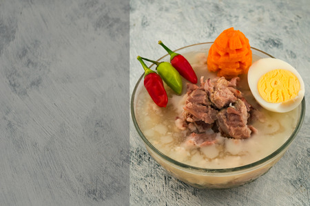 Beef jelly in a glass plate. Small hot pepper. Half boiled egg. Light background. Copy space. Raw sliced carrots.