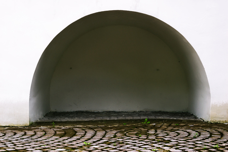 A semicircular alcove in the white wall. Paved sidewalk. Footpath.