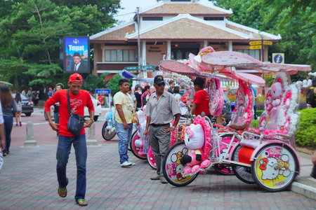 favorite colour: Melaka, Malaysia - January 02 2016: Trishaw decorated with colorful flowers and doll. snap the picture looks a little blur while running.