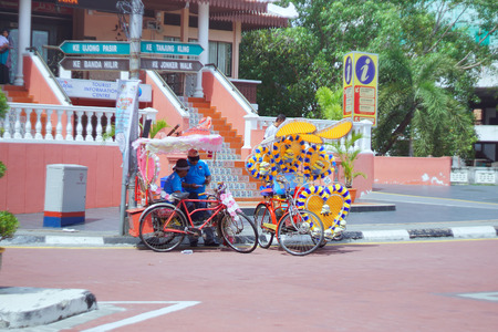 trishaw: Melaka, Malaysia - January 02 2016: Trishaw decorated with colorful flowers and doll. snap the picture looks a little blur while running.