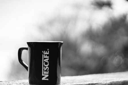 nescafe: TERENGGANU, MALAYSIA - 09022016 : Outdoor shot of a black and white Nescafe cup, background blur. Editorial