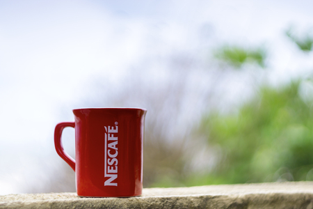 nescafe: TERENGGANU, MALAYSIA - 09022016 : Outdoor shot of a red Nescafe cup, background blur.