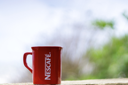 flagship: TERENGGANU, MALAYSIA - 09022016 : Outdoor shot of a red Nescafe cup, background blur.