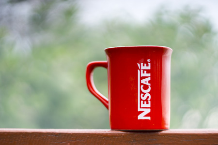 TERENGGANU, MALAYSIA - 09022016 : Outdoor shot of a red Nescafe cup, background blur.